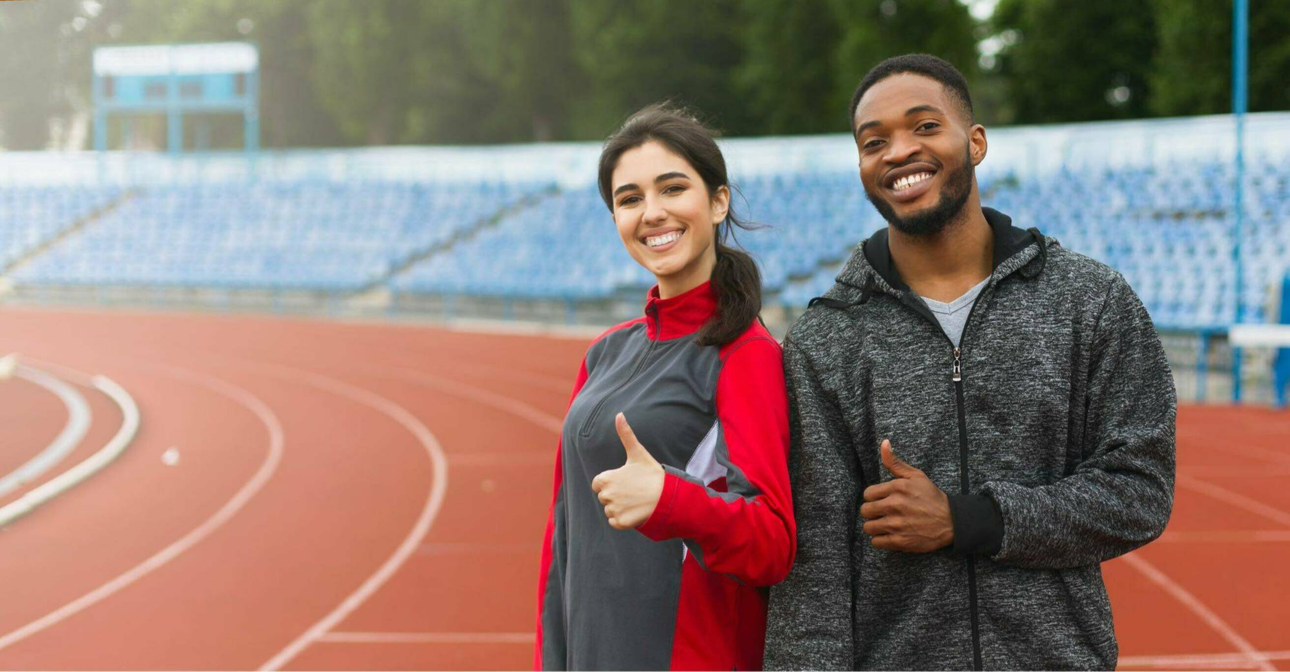 Man and woman stand on track and give thumbs up gesture2