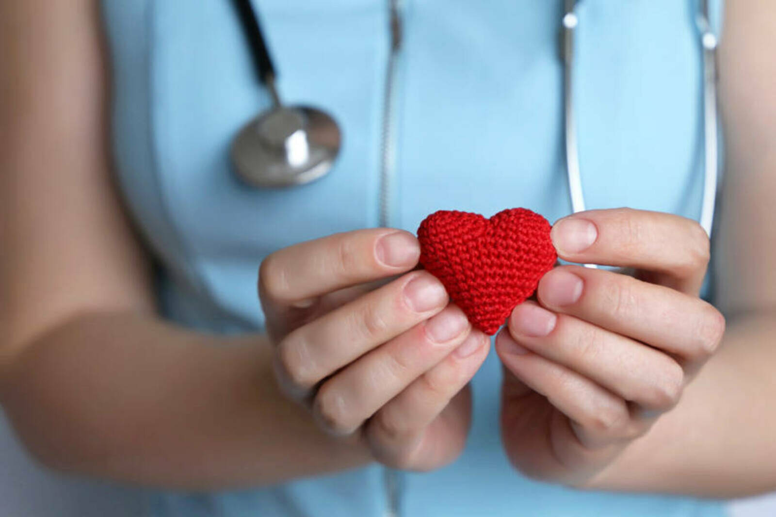 Woman doctor holding red knitted heart in hands